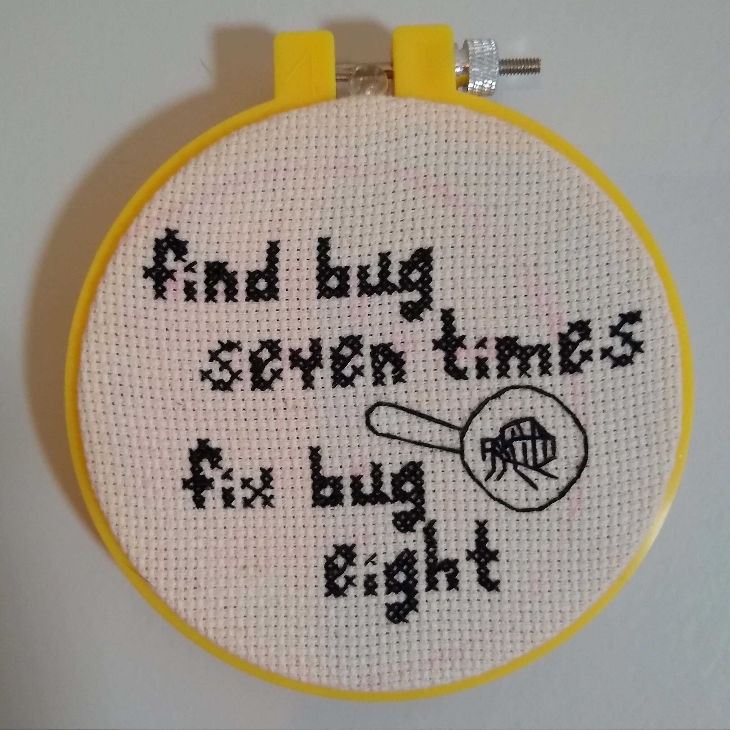 cross-stitch of a flea in a magnifying glass that says 'find bug seven times, fix bug eight'