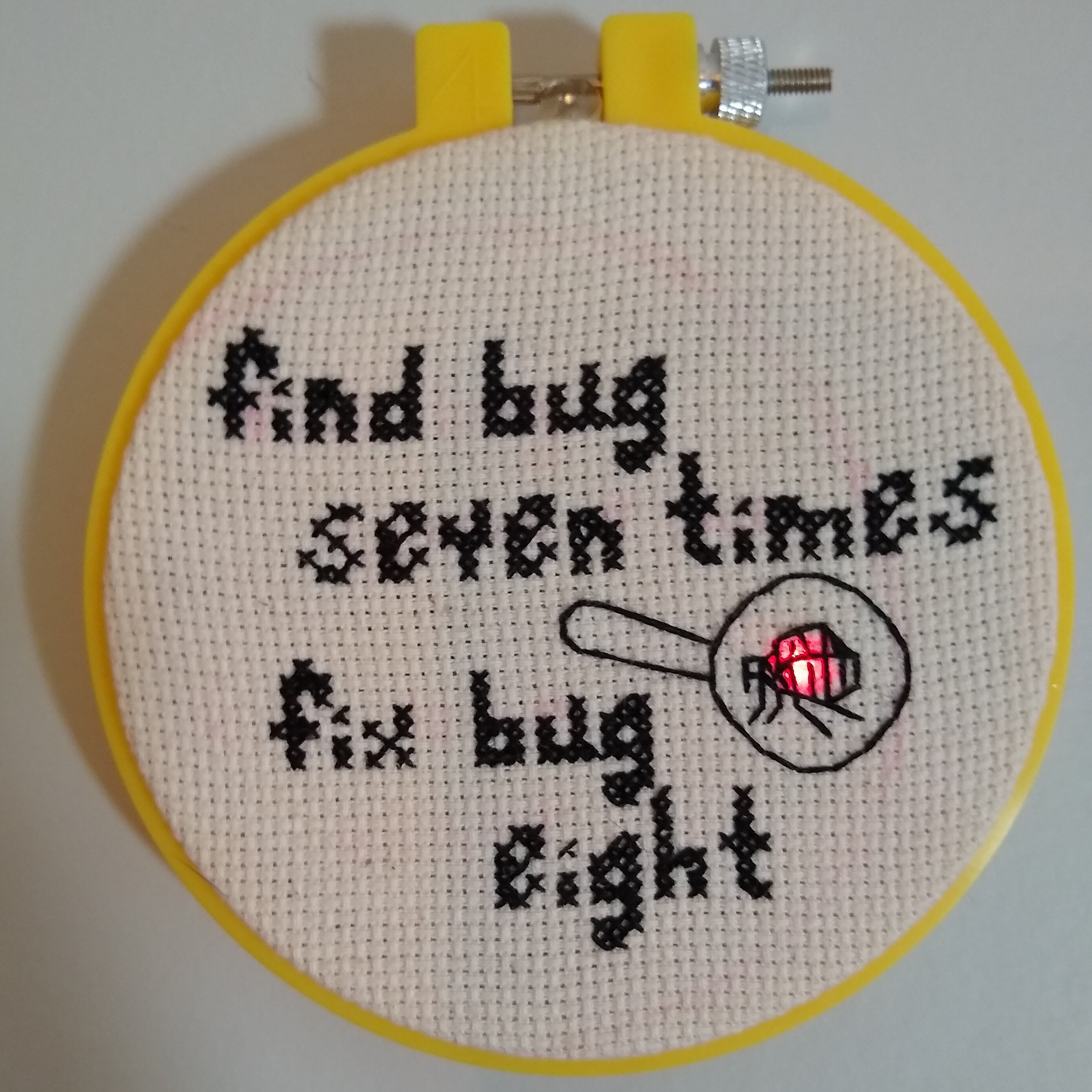 cross-stitch of a flea in a magnifying glass lit up with a red LED. it says 'find bug seven times, fix but eight'